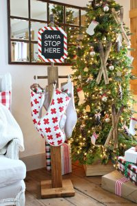 'Santa Stop Here' sign serves as a stocking hanger, too!