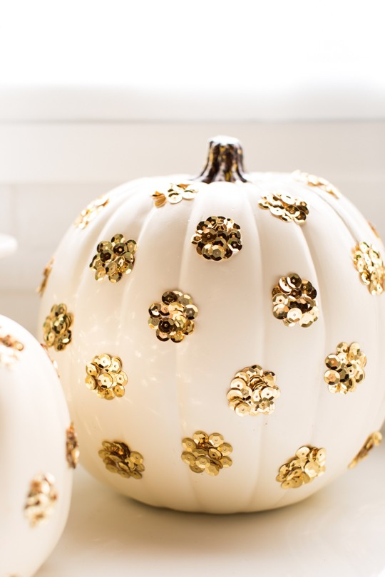 Paint your pumpkin white and using dots of glue, embellish it with gold sparkling sequins for a stylish look.