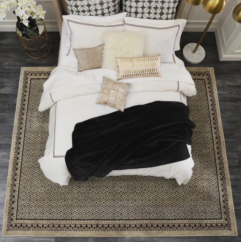Overhead view of full size bed, nightstand and lamp, with area rug placed under 3/4 of the bed.