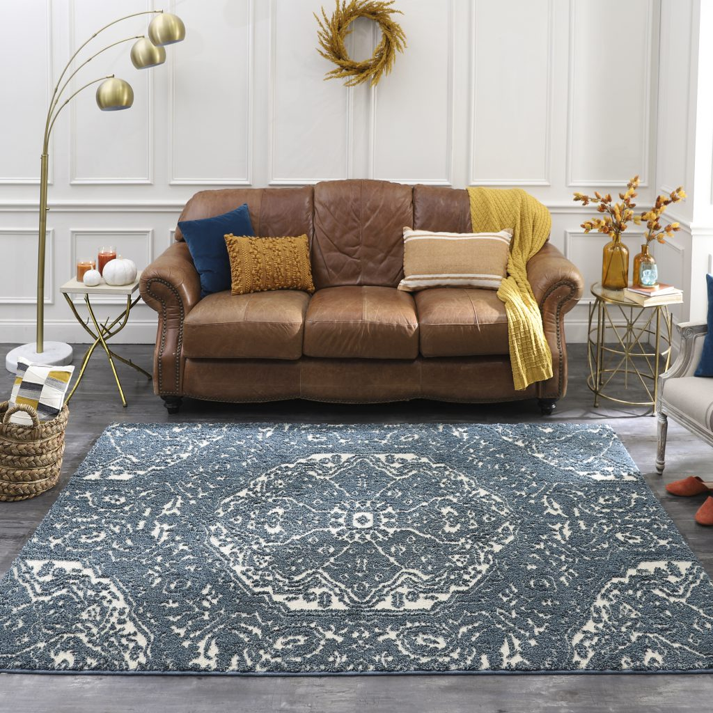 Blue Francesca area rug is shown with small sofa and single side chair.