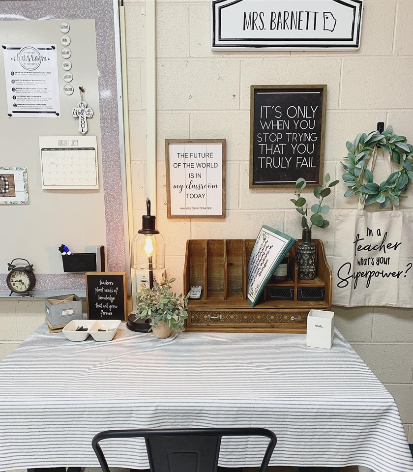 Adorable workspace with farmhouse accents like a eucalyptus wreath, Edison table lamp and wooden mail sorter.