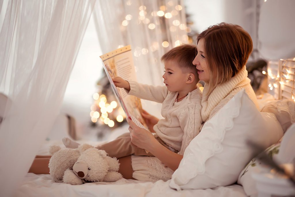 Mom reads a book to her son during the holidays
