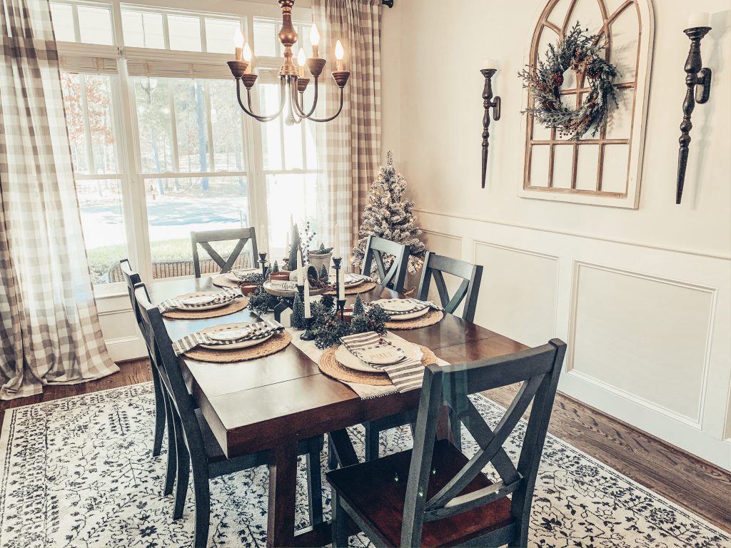 A picture containing a dining room table decorated for Christmas.