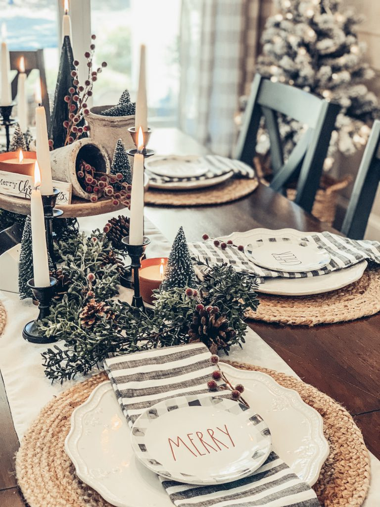 A holiday tablescape with Rae Dunn plates, candles, and greenery with pinecones and red berries
