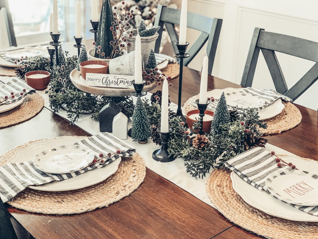A table decorated for Christmas with bottle brush trees, candles, jute placemats and red berries.